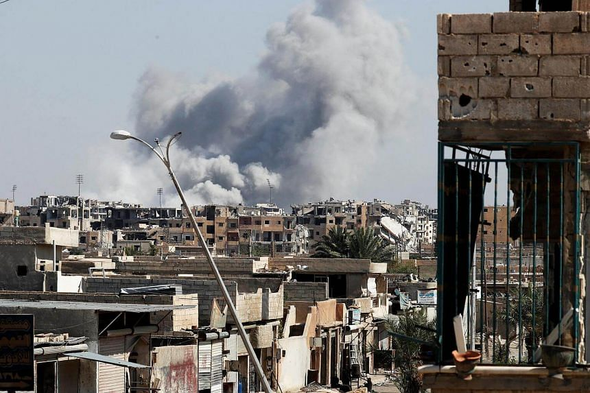 Smoke rises near the stadium where the Islamic State militants are holed up after an air strike by coalition forces at the frontline, in Raqqa, on Oct 12, 2017.