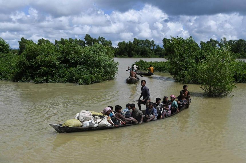 At least five people were killed and dozens left missing after a boat packed with Rohingya refugees fleeing Myanmar's Rakhine state for Bangladesh sank in a river that separates the two nations.