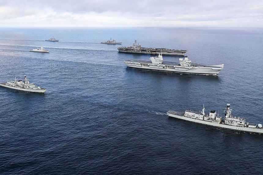 The Royal Navy aircraft carrier HMS Queen Elizabeth (second, right) off the coast of Scotland, alongside (from left) HMS Iron Duke, HMNOWS Helge Ingstad, USS Donald Cook, USS Philippine Sea, USS George H W Bush and HMS Westminster, on Aug 8, 2017.