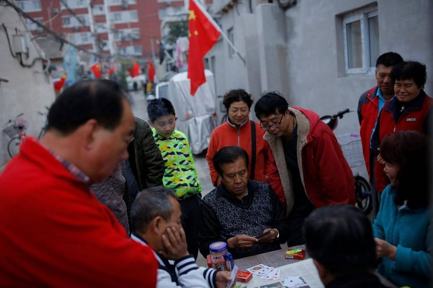 People play cards in a hutong alley that is decorated with Chinese national flags in an old part of Beijing as the capital prepares for the 19th National Congress of the Communist Party of China, on Oct 15, 2017.