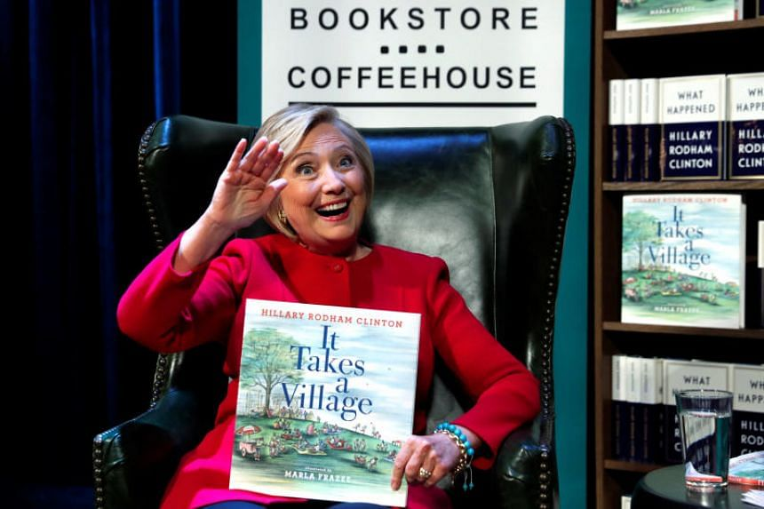 Former US Secretary of State Hillary Clinton, holding a copy of her children's book, takes the stage to discuss her new book What Happened as she launches a 15-city book tour at the Warner Theatre in Washington, US on Sept 18, 2017.