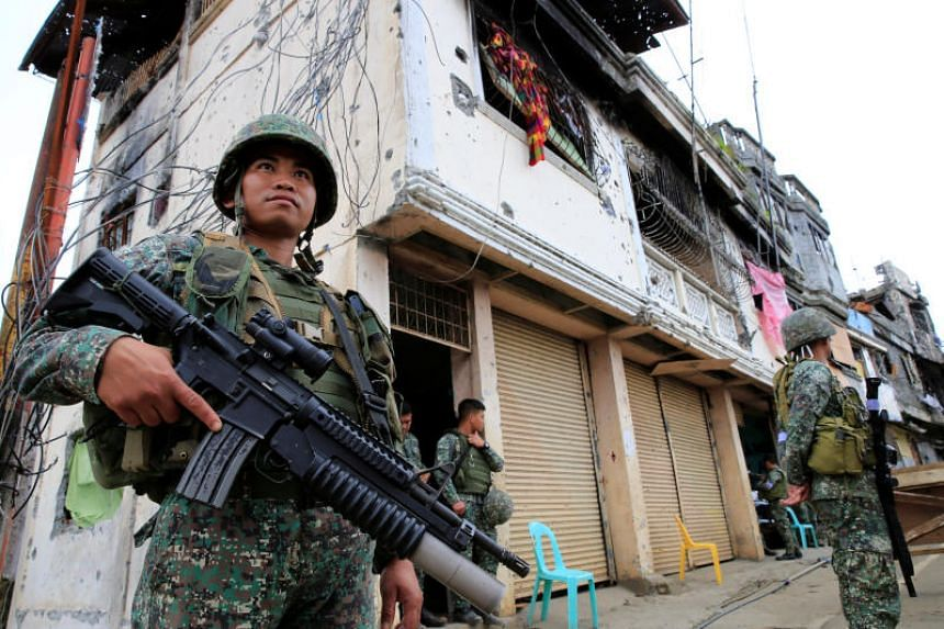 Government soldiers stand guard in front of damaged building and houses in Sultan Omar Dianalan boulevard at the Mapandi district in Marawi city, on Sept 23, 2017.