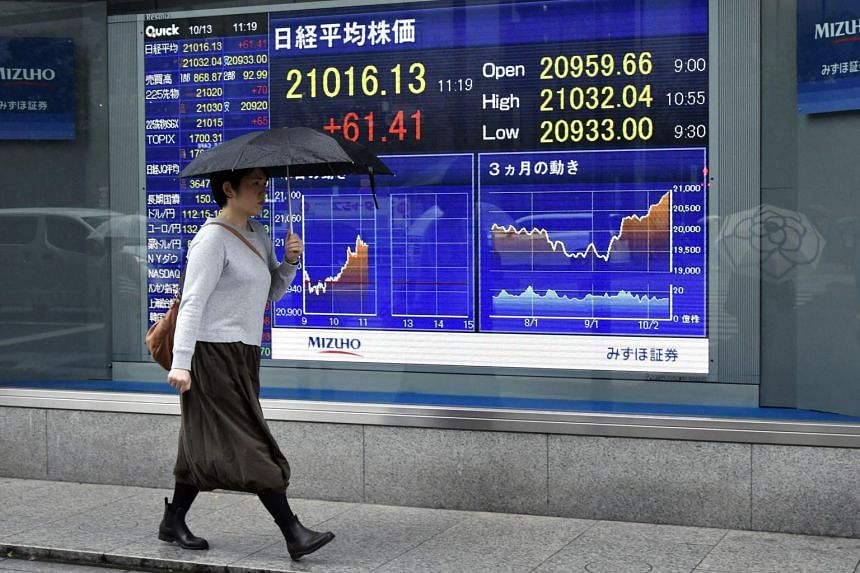 A pedestrian walks past a stock market indicator board in Tokyo. Japan's Nikkei is up 0.5 per cent and South Korea's stock index set a new record with an increase of 0.3 per cent.