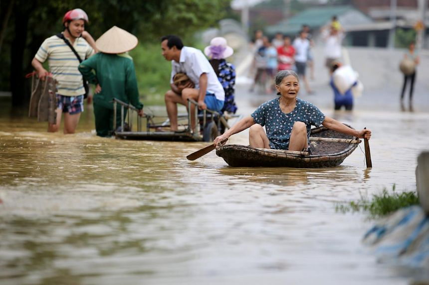 People travel through a flooded area in Hoang Van Thu commune, Chuong My district in Hanoi, Vietnam, on Oct 13, 2017.
