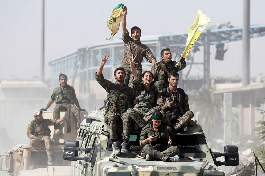 Syrian Democratic Forces fighters celebrate victory in Raqqa, Syria, Oct 17, 2017.