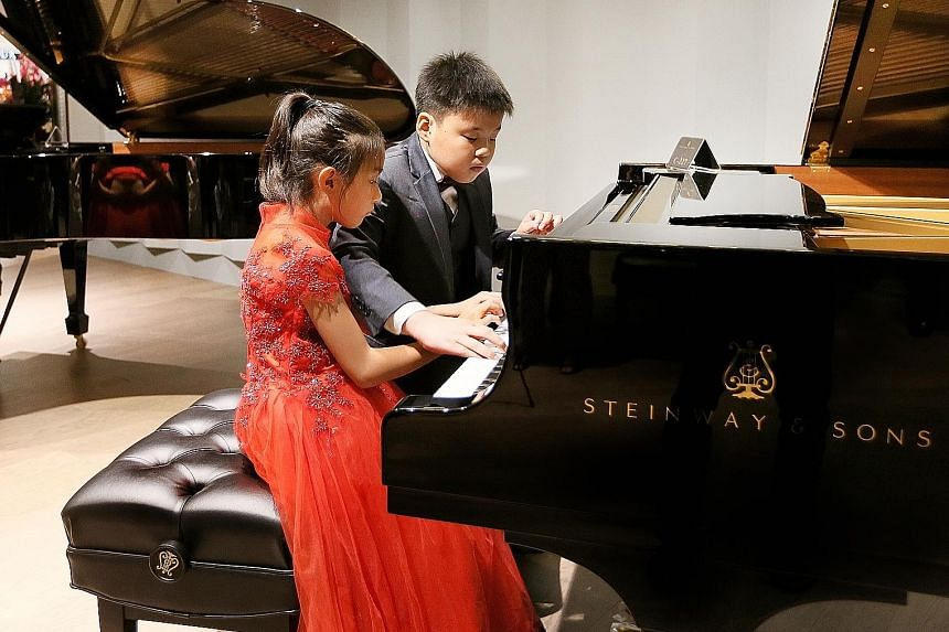 Award-winning pianists Kion Chew (in red), nine, and Ryan Phuan, 10, playing Mozart's Papageno, an aria from the opera, The Magic Flute, at the opening of the new Steinway Gallery at Ion Orchard yesterday. The duo will be performing at ChildAid 2017,
