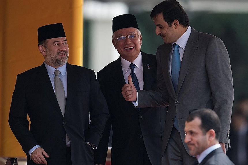 From left: Malaysia's King Sultan Muhammad V, Prime Minister Najib Razak and Qatar's Emir Sheikh Tamim bin Hamad al-Thani in Kuala Lumpur yesterday. The Qatar ruler was on a visit to Malaysia at the invitation of the King and was honoured with a stat