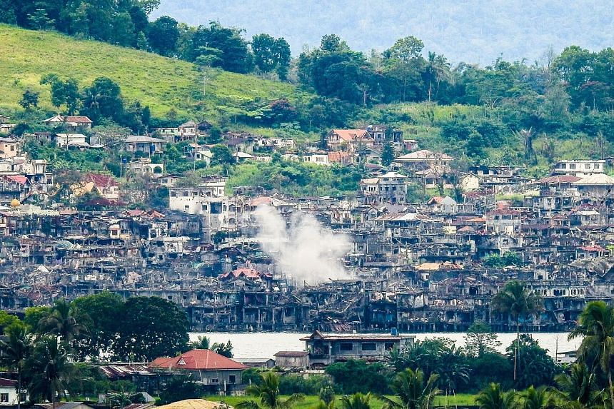 Smoke billowing from destroyed buildings after government troops fired mortars at an ISIS position in Marawi on the southern island of Mindanao on Sunday.