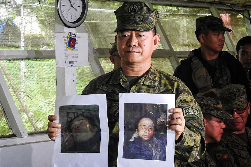 Philippine military chief General Eduardo Ano shows images of Islamic militant leaders Isnilon Hapilon (right) and Omarkhayam Maute (left) during a press conference at a military camp in Marawi,on Oct 16, 2017.