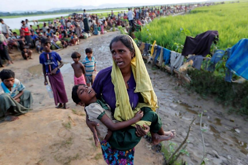 A Rohingya refugee woman carries her daughter and searches for help as they wait to receive permission from the Bangladeshi army to continue their way to the refugee camps, in Palang Khali, Bangladesh, on Oct 17, 2017.