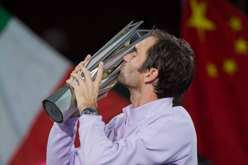 Roger Federer kisses the trophy after winning his men's final singles match against Rafael Nadal of Spain at the Shanghai Masters tennis tournament in Shanghai on Oct 15, 2017.