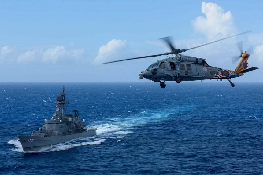 A US MH-60S Sea Hawk flies by Japan's Maritime Self-Defense Force ship JS Shimakaze above waters around Okinawa on Oct 9, 2017. Some 62 per cent of Japanese are worried over concerns about US President Donald Trump's global leadership.