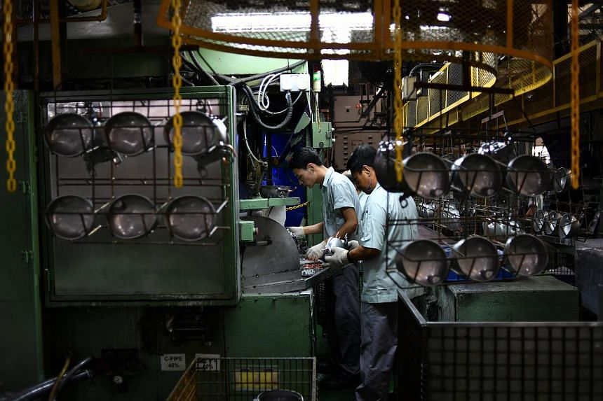 Workers at Panasonic's refrigerator compressor factory located in Bedok. The economy was lifted in large part by the manufacturing sector, which surged 15.5 per cent year on year.
