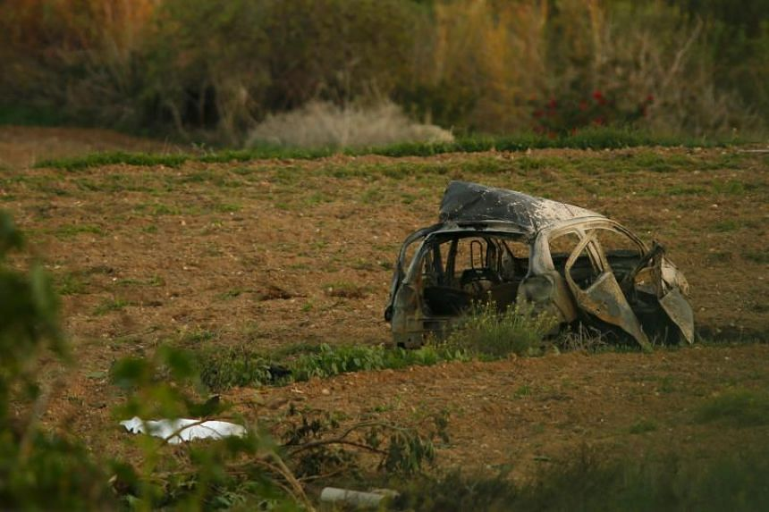 A white sheet covers the body of investigative journalist Daphne Caruana Galizia after a powerful bomb blew up her car in Bidnija, Malta, on Oct 16, 2017.