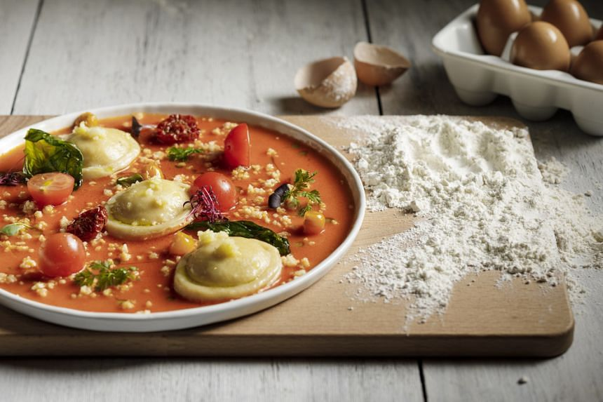 Indulge in homemade ravioli filled with ricotta and smoked scamorza cheese caprese style, a treasured family recipe from the chefs' father.