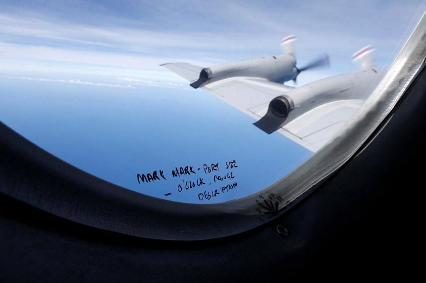 Hand-written notes on how a crew member should report the sighting of debris in the southern Indian Ocean is pictured on a window aboard a Royal New Zealand Air Force P-3K2 Orion aircraft searching for missing Malaysian Airlines flight MH370, on Marc