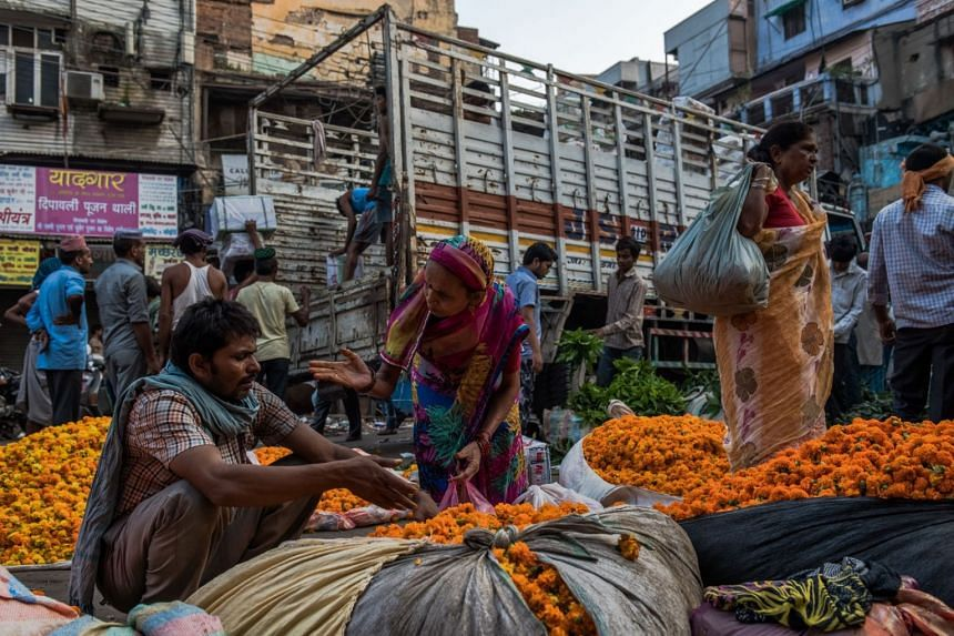 A resident buys flowers from a vendor at a market in New Delhi. Today all indicators of economic health of the country indicate a comfortable position, which the finance minister calls the 'Bright Spot' of the Indian economy.