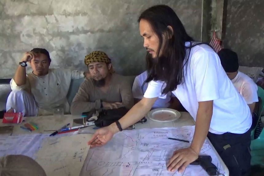 An image from a video released by the Philippine army showing Isnilon Hapilon (second from left) looking at an improvised map of Marawi with Abdullah Maute (right), the brother of Omarkhayam Maute. All three leaders of the Marawi terrorists are now c