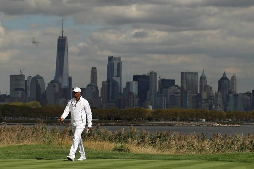 Tiger Woods, captain's assistant of the US team, walking in front of the New York City skyline during the Presidents Cup at Liberty National Golf Club on Sept 29, 2017 in Jersey City, New Jersey.
