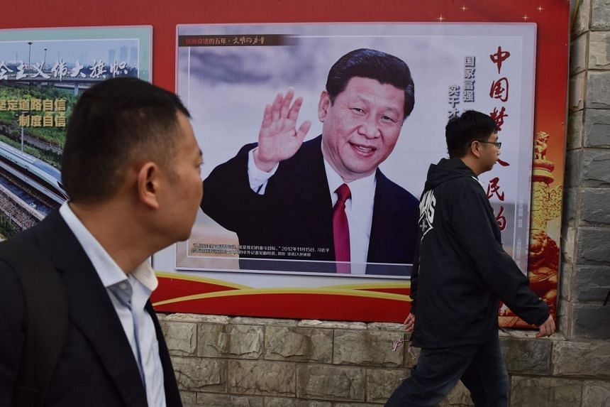 People walk past a poster featuring Chinese President Xi Jinping in Beijing on Oct 16, 2017. Markets will be listening when Mr Xi addresses more than 2,000 delegates in Beijing to kick off the conclave.