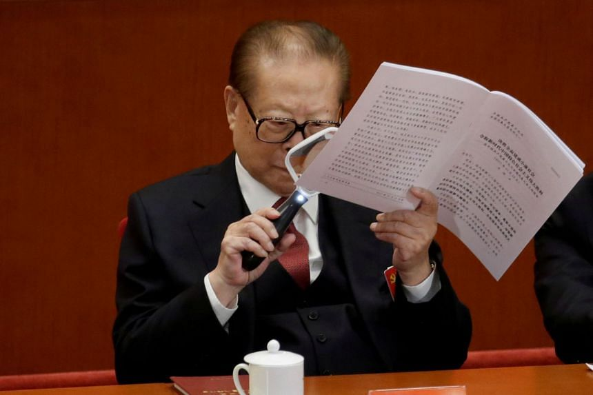 Former Chinese President Jiang Zemin uses a magnifier as he reads Chinese President Xi Jinping's report during the opening of the 19th National Congress of the Chinese Communist Party.