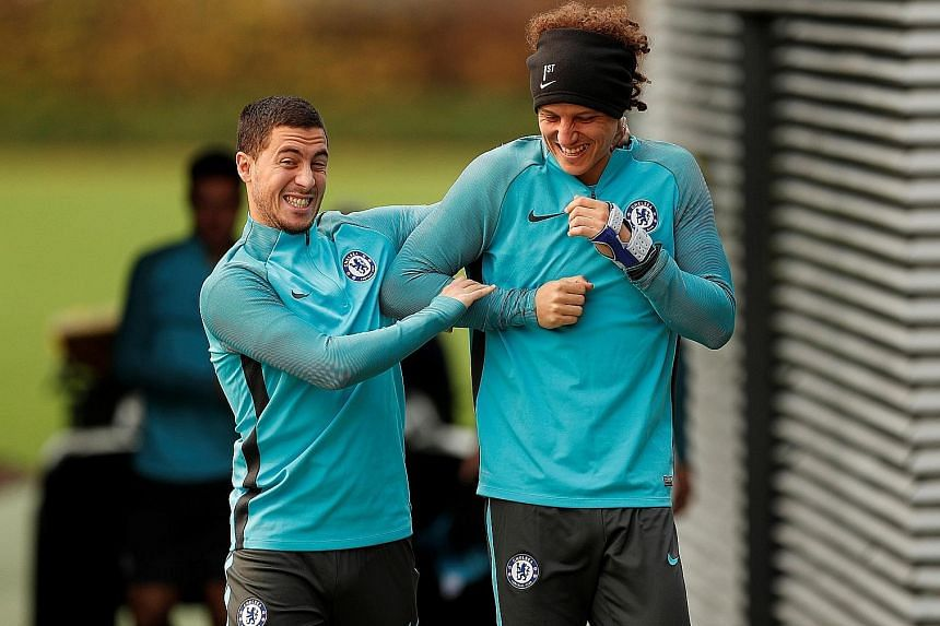 Chelsea's Eden Hazard (left) and David Luiz enjoying a light moment during a session at Cobham Training Centre in London yesterday ahead of their home Champions League match against Italian Serie A side Roma. An underwhelming start with three losses
