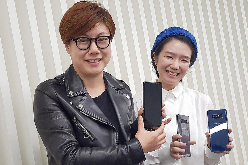 Product designers Lee Ji Young (left) and Lee Sae Hee, of Samsung's mobile communications business, with the Galaxy Note8 which they helped design.