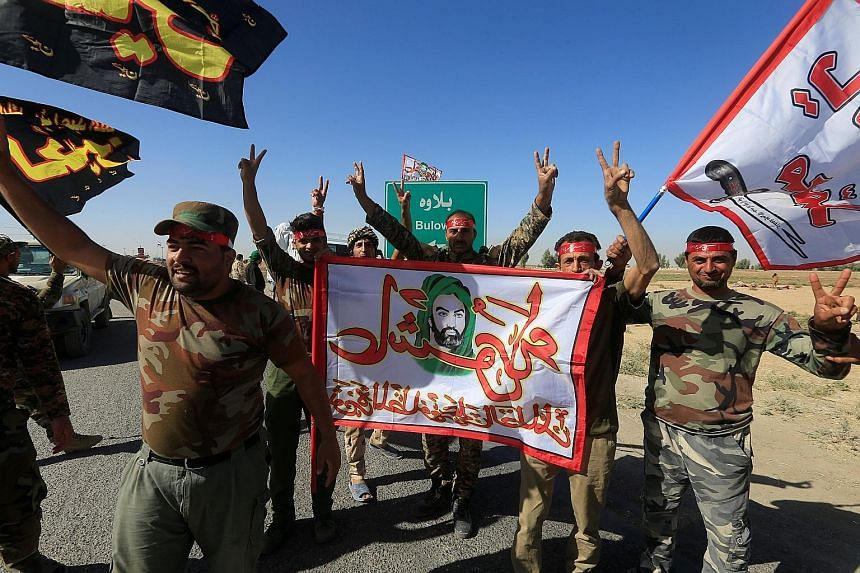 Shi'ite forces celebrating on the outskirts of Kirkuk yesterday. Iraqi forces and allied Iranian-backed militias have pressed their campaign to retake oil-rich territory from Kurdish forces, capturing the town of Sinjar.