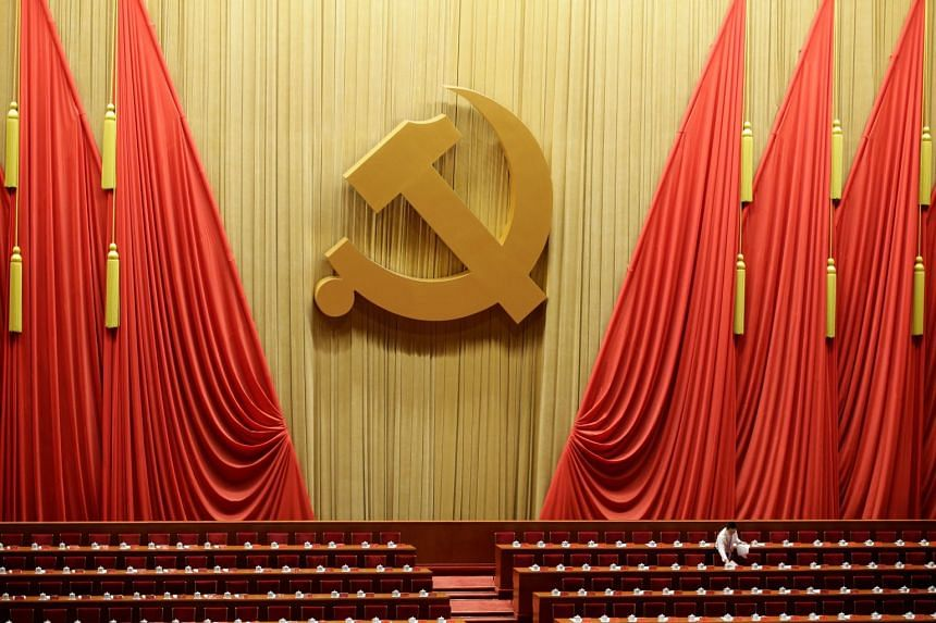 A staff member prepares reports for delegates inside the Great Hall of the People before the opening of the 19th National Congress of the Communist Party of China in Beijing.
