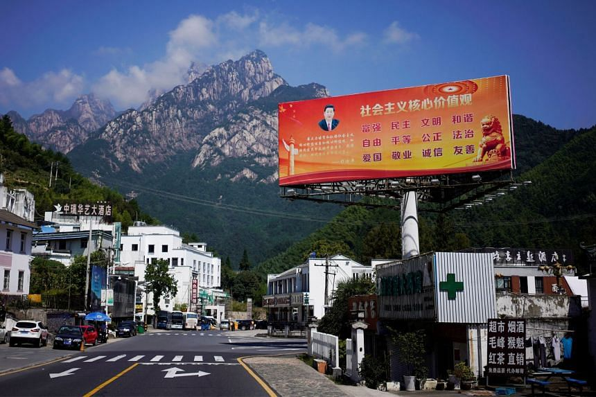 """A poster with a portrait of Chinese President Xi Jinping overlooks a street in Huangshan, Anhui province, China, on Sept 16, 2017.  Mr Xi, on Oct 18, 2017, vows to keep up the country's years-long battle against smog to ensure """"blue skies"""" and promot"""