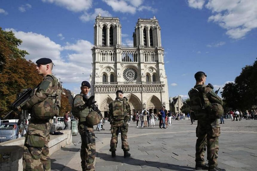 French soldiers of the Operation Sentinelle security mission as they stand alert outside the Notre-Dame de Paris Cathedral in Paris on Aug 20, 2017.