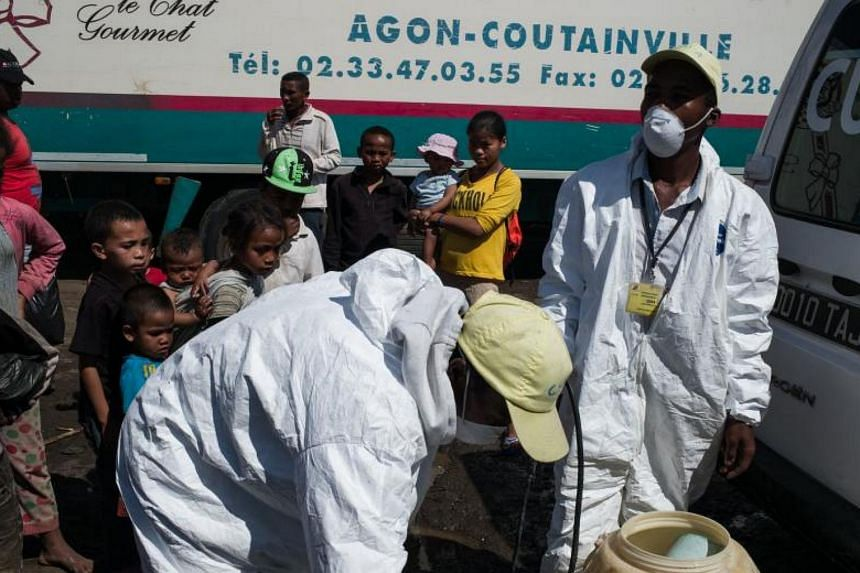 Council workers prepare to spray disinfectant during the clean-up of the market of Anosibe in the district of Antananarivo on Oct 10, 2017.