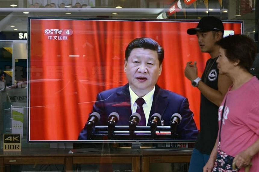 Local residents walk past a monitor showing a broadcast from Beijing of Chinese leader Xi Jinping speaking at the 19th Communist Party Congress, in Taipei on Oct 18, 2017.