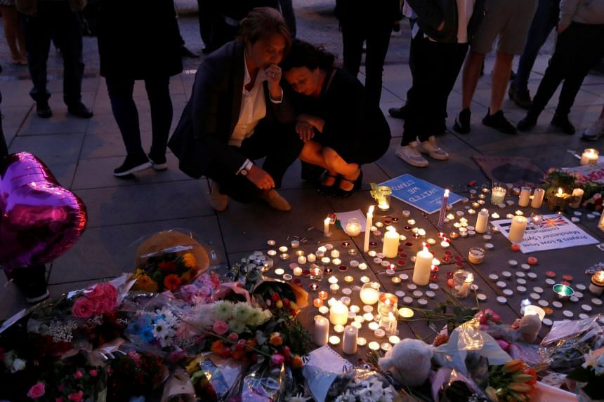 Members of the public paying their respects following a vigil for the victims of the Manchester Arena bombing, in Manchester on May 23, 2017.