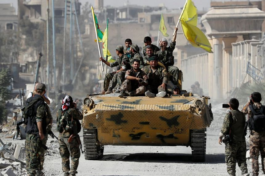 Fighters of Syrian Democratic Forces ride atop of an armoured vehicle after Raqqa was liberated from the Islamic State militants, in Raqqa, Syria on Oct 17, 2017.