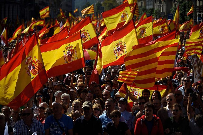 "Protesters hold Spanish flags during a demonstration called by ""Societat Civil Catalana"" (Catalan Civil Society) to support the unity of Spain on Oct 8, 2017 in Barcelona."