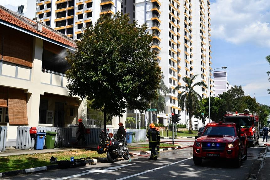 SCDF officers fighting the fire, which broke out on the second floor of the terrace house.