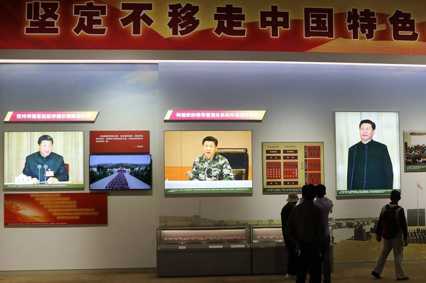 Visitors looking at photos of Chinese President Xi Jinping on display at the Five Years Of Sheer Endeavor exhibition at the Beijing Exhibition Centre on Sept 28, 2017.