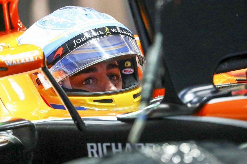 Alonso sits in his car during the second practice session of the Japanese Formula One Grand Prix.
