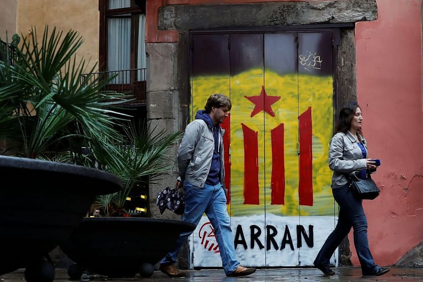 Pedestrians pass by a doorway painted in the colours of the Catalan seperatist flag in Barcelona, Oct 19, 2017.