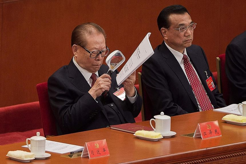 Former Chinese president Jiang Zemin reading the text of President Xi Jinping's speech as he listened to the address beside Premier Li Keqiang during the opening of the 19th Communist Party Congress in Beijing yesterday. The 91-year-old former party