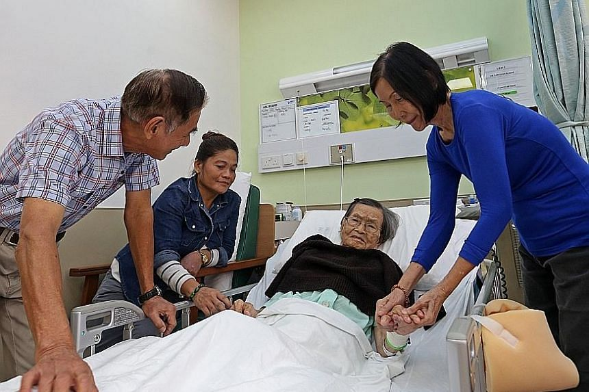 """Madam Liew Tim in NUH's Silver Unit this month with her son Wong Weng Yoi, daughter Brenda Wong (at right) and maid Juliana Abes Barang. Another son, Mr Wong Wing Chow, said of the Silver Unit: """"It's a better environment - you don't have noise like i"""