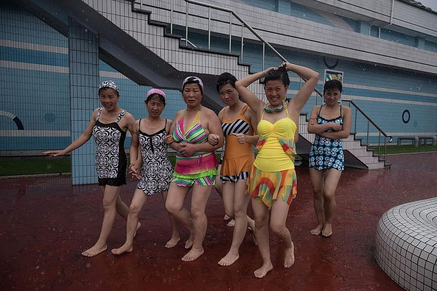 In Pyongyang, women wear brightly coloured swimsuits to the pool (top) and flowy dresses with high heels (above).