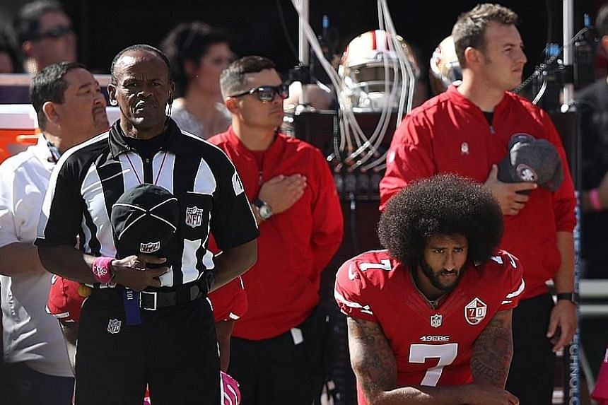 """Former San Francisco 49ers quarterback Colin Kaepernick """"taking a knee"""" last October before his NFL game against the Tampa Bay Buccaneers in protest at the racial inequality in the US and police treatment towards African Americans."""