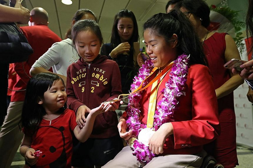 Rio Paralympics double champion Yip Pin Xiu showing her medals to her then four-and 10-year-old nieces Shernice Ang and Chew Xiu Wen at Changi Airport in September last year upon her return.