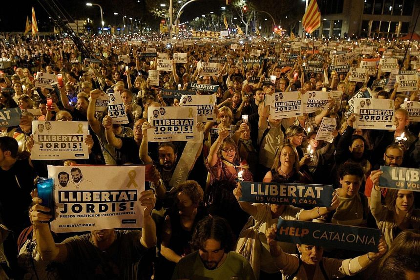 """Catalans with placards reading """"freedom"""" during a demonstration in Barcelona on Tuesday night against the arrest of two separatist leaders."""