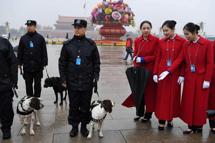 Attendants look at sniffer dogs while posing for photos in Tiananmen Square during the opening ceremony of the 19th Communist Party Congress in Beijing.