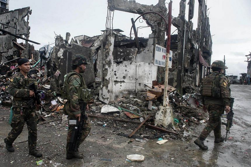 Filipino soldiers conduct patrol next to bombed-out buildings in the ruined city of Marawi, on Oct 17, 2017.