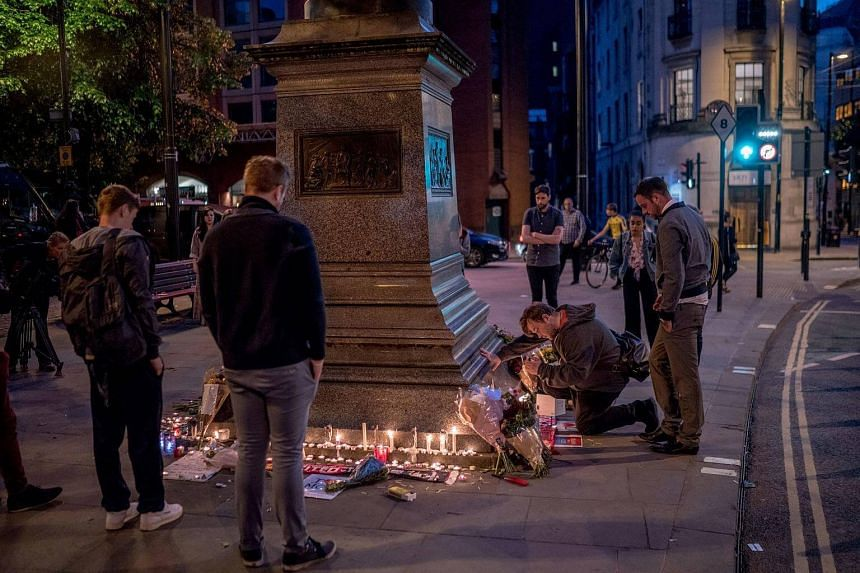 People light candles at a makeshift memorial to victims of the Manchester Arena bombing, at Albert Square in Manchester, on May 23, 2017.