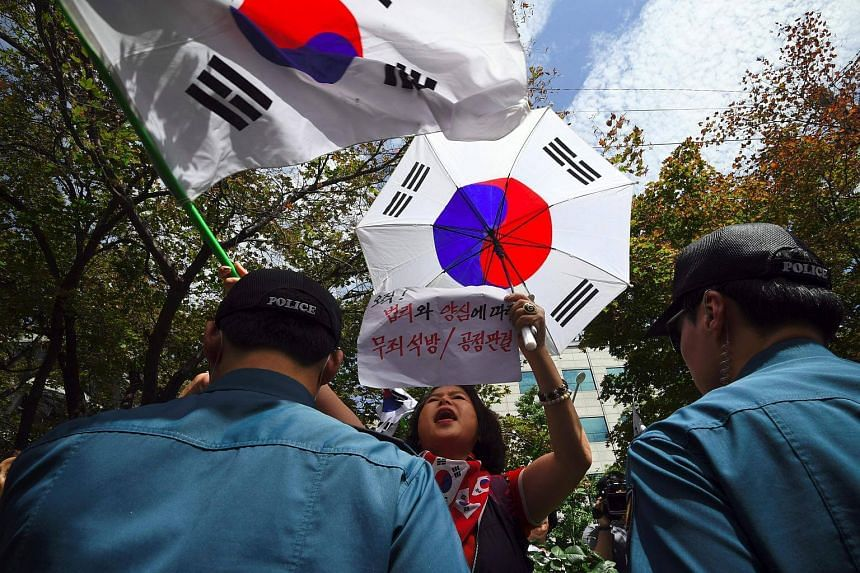 Supporters of South Korea's ousted president Park Geun Hye wave national flags during a rally demanding the release of Samsung heir Lee Jae Yong outside the Seoul Central District Court.